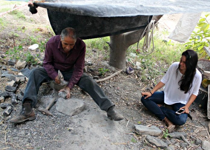 Two people sitting on ground, one making utensil (Courtesy of Sofia Cruz del Río Castellanos)