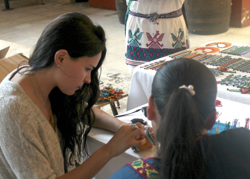 Cruz del Río and woman sitting at table working with beads (Courtesy of Sofia Cruz del Río Castellanos)