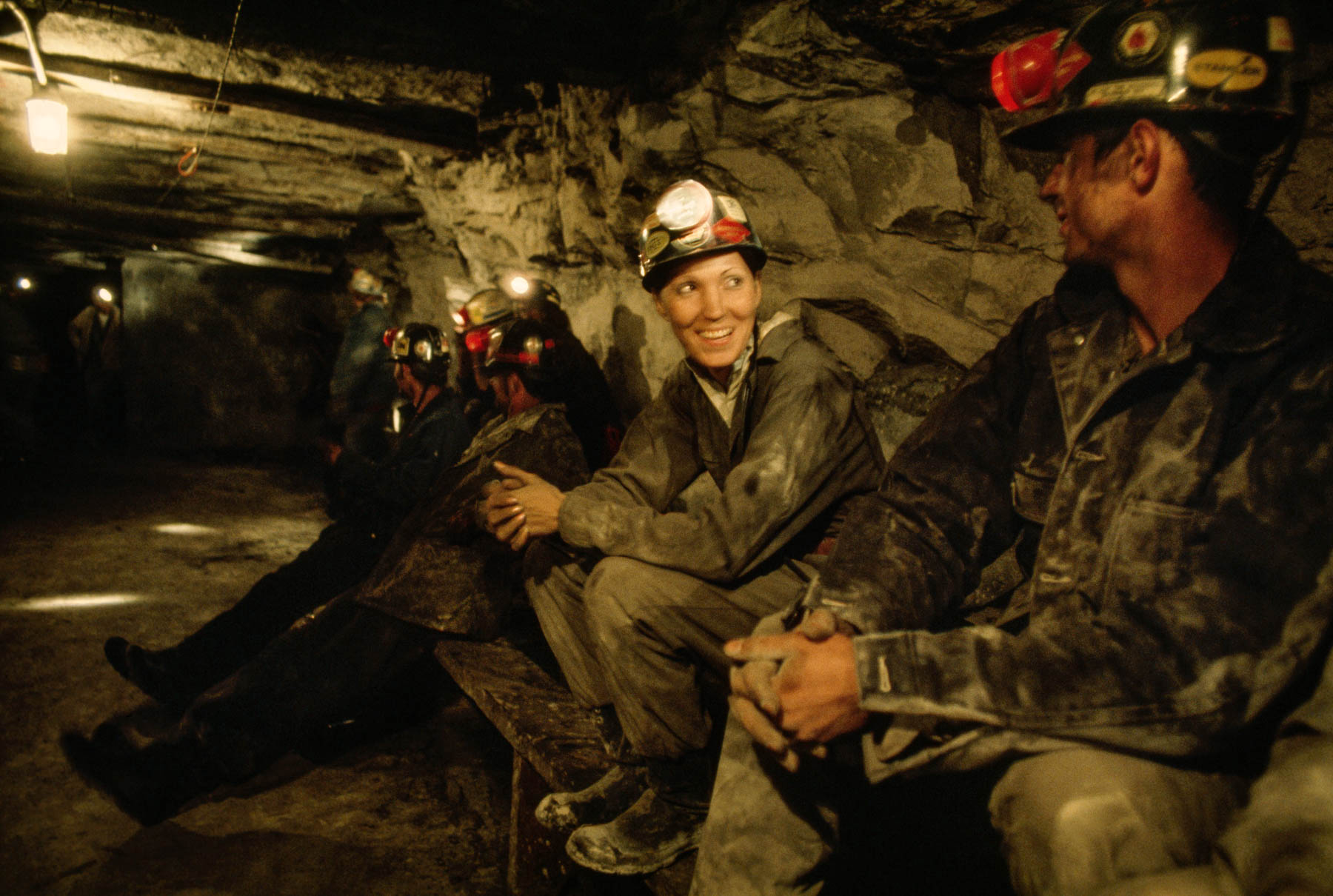 Woman sitting, smiling in coal mine next to other miners (© Jodi Cobb/National Geographic Creative)