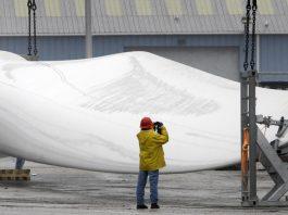 Man taking photo of huge, white wind turbine blade (© AP Images)