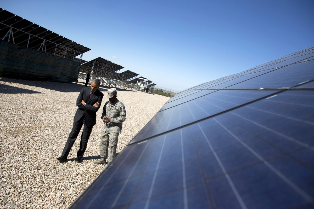 Two men walking by solar panels (© AP Images)