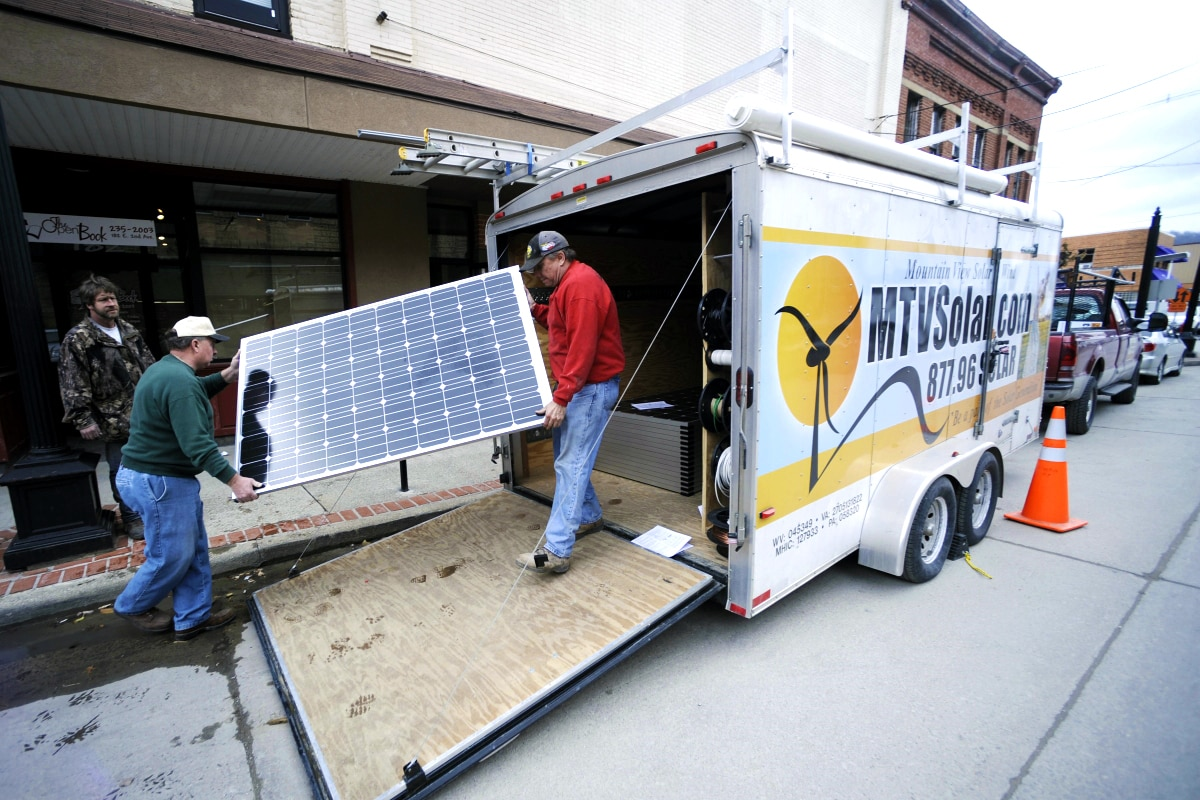 Two men carrying a solar panel off a truck (© AP images)