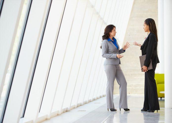 Two women talking in glassed-in hallway (© Shutterstock/Monkey Business Images)
