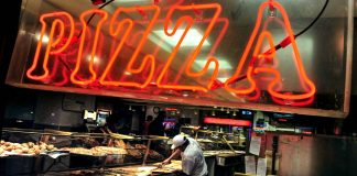 Neon pizza sign and man preparing several pizzas (© AP Images)