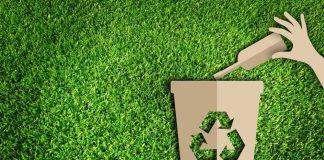 Recorte de cartón de reciclaje sobre el césped (Shutterstock)