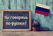 """Una pizarra con la pregunta """"¿Hablas ruso?"""" escrito en ruso al lado de lápices, libros y una pequeña bandera rusa (Shutterstock)"""