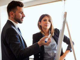 Man and woman standing at flip chart (© Shutterstock)