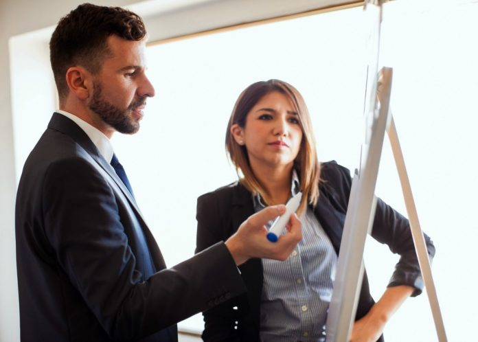Man and woman standing at flip chart (© Shutterstock)