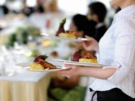 Waitress carrying three plates of food (© Shutterstock)