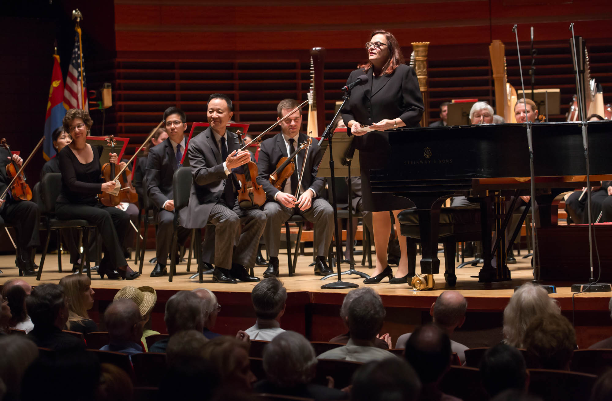 Woman standing at microphone onstage among sitting orchestra members (© Jessica Griffin/Philadelphia Orchestra)