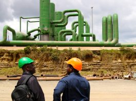 Two workers in hard hats, with geothermal plant in background (Carole Douglis/USAID West Africa)