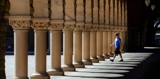 Man walking toward building columns (© AP Images)