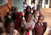 Niños keniatas de pie al lado de un edificio (© AP Images)