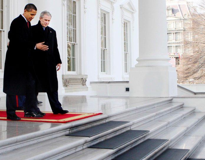 Barack Obama e George Bush caminham em direção à escadaria na Casa Branca (© AP Images)