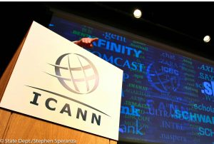 ICANN logo on lectern with hand above it pointing outward (© AP Images)