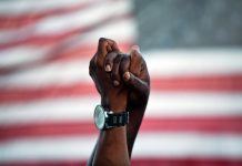 Two clasped African-American hands raised in front of American flag (© AP Images)