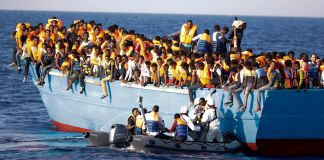 People in overcrowded boat, smaller boat alongside (© AP Images)