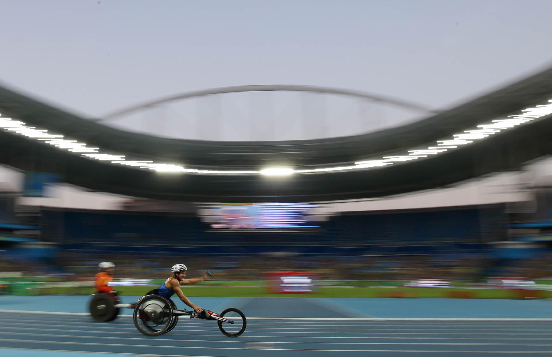 Woman in wheelchair race raising arm (© AP Images)