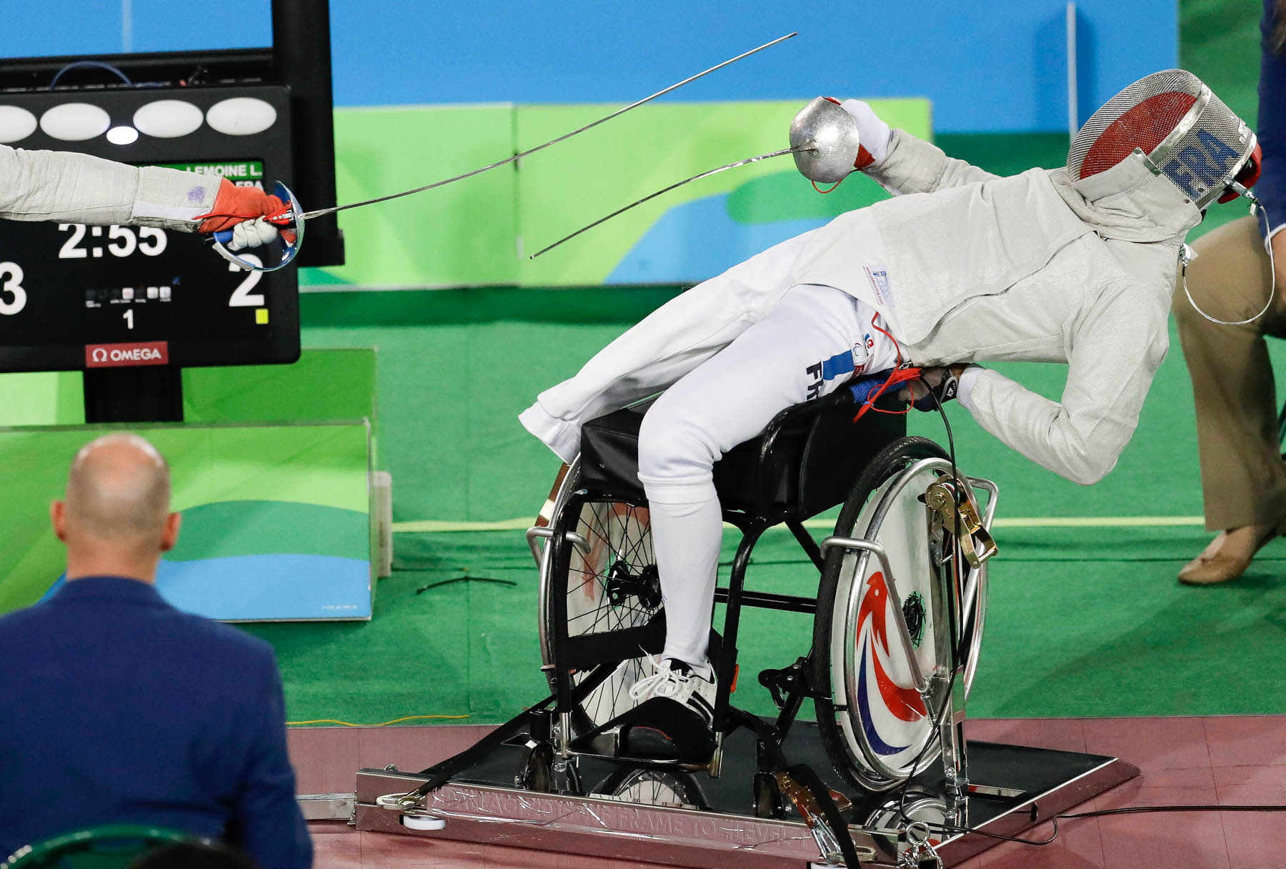 Fencer in wheelchair twisting to avoid saber (© AP Images)