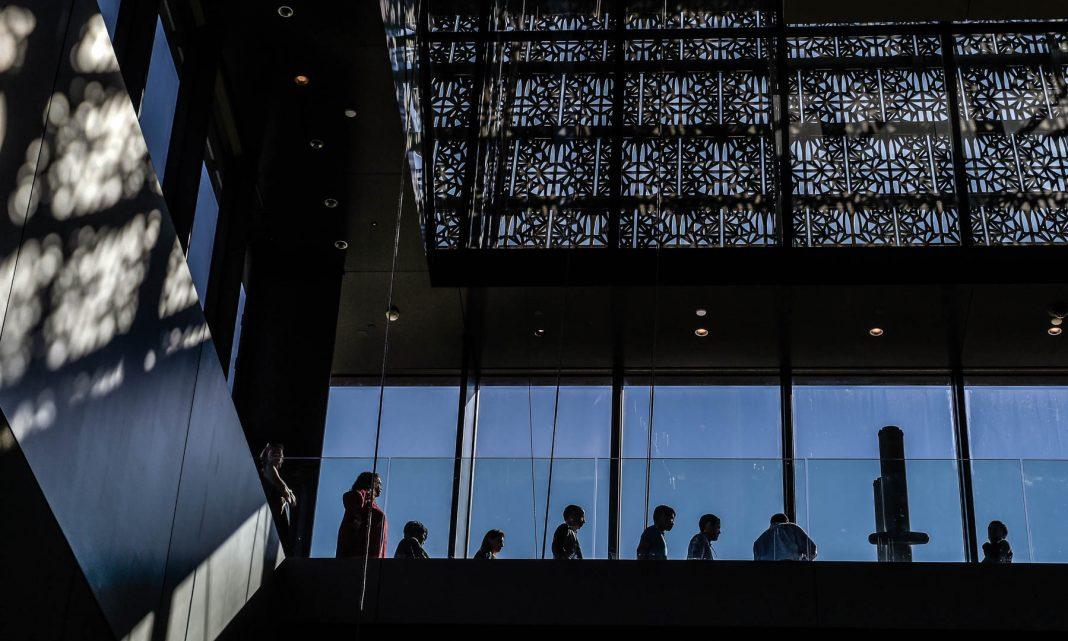 Gente parada cerca de ventanas (© AP Images)