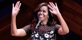 Michelle Obama onstage at microphone, gesturing (© AP Images)