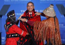 Two people wrapping blanket around President Obama's shoulders (@ AP Images)
