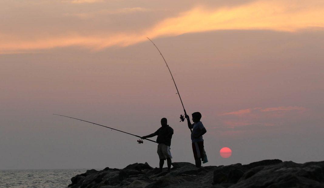 Duas pessoas pescando ao pôr do sol (© AP Images)