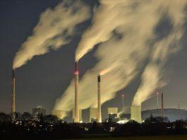 Night shot of smokestacks releasing gases (© AP Images)