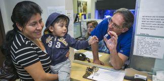 Médico segurando uma ampola de vacina em frente a uma mãe e uma criança (© AP Images)