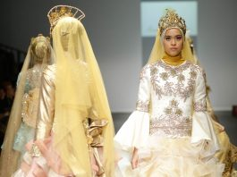 Models on runway wearing elaborate hijabs and gowns (© AP Images)
