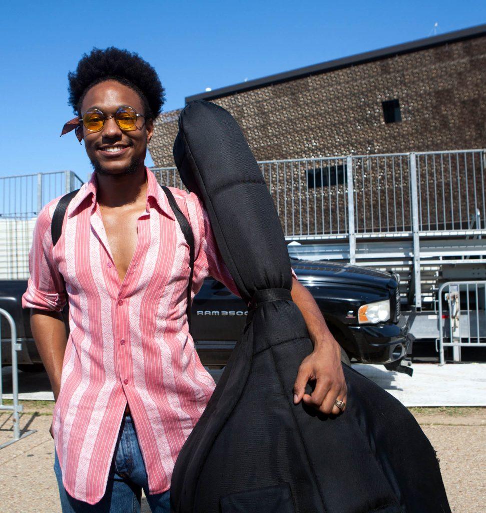 Un homme, devant le musée, tenant un violoncelle dans son étui (Département d'État/D.A Peterson)