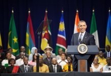 President Obama at lectern, young Africans seated behind him (State Dept./D.A. Peterson)