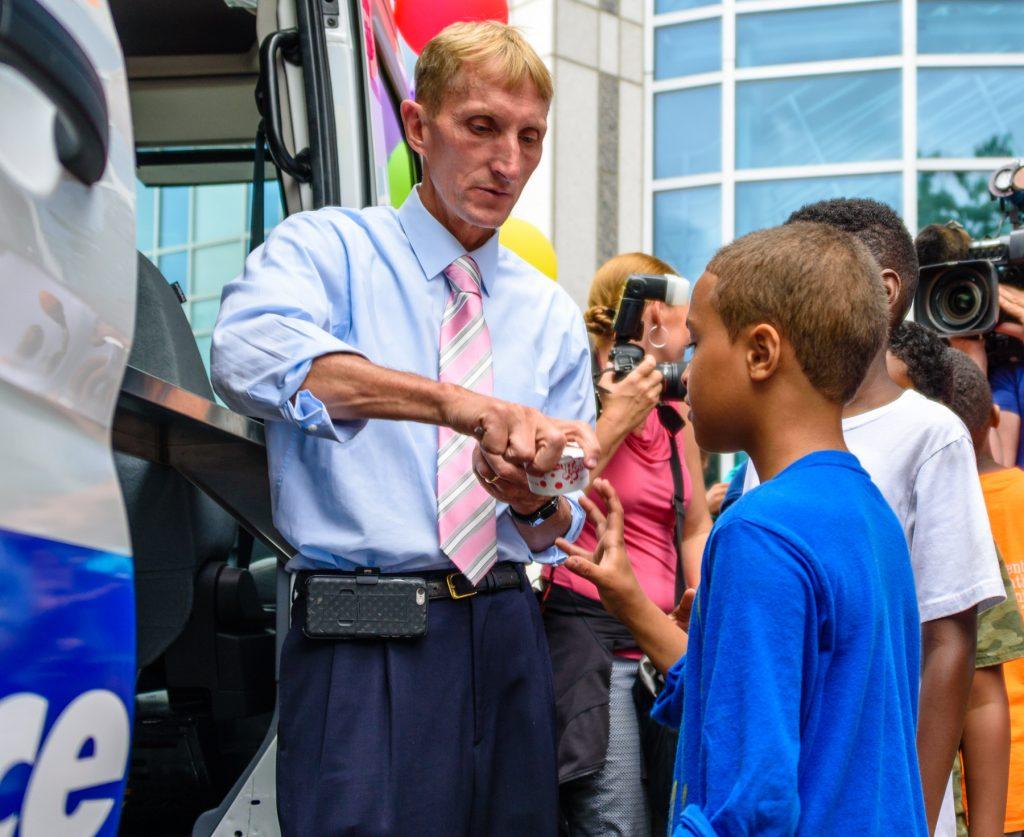 Un homme ouvrant une petite coupe de glace en carton pour un enfant (Photo offerte par la police de Boston)