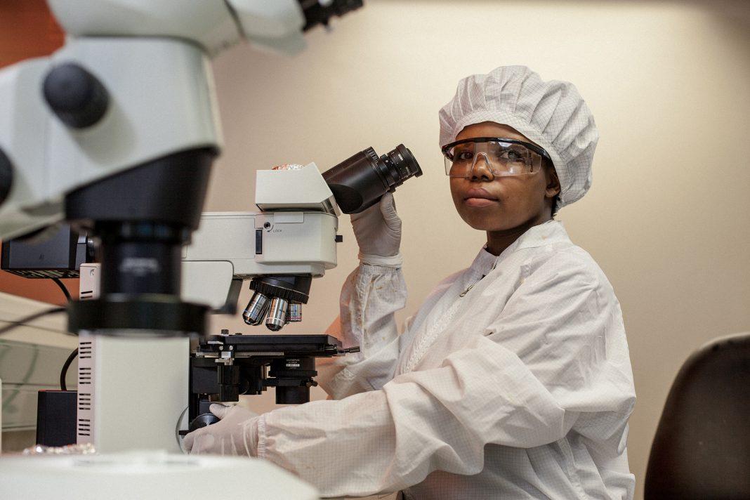 Mulher com roupa hospitalar sentada diante de um microscópio (Cortesia: Instituto de Pesquisa para TB-HIV de KwaZulu-Natal)