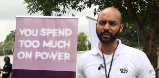 Man standing next to sign reading 'You spend too much on power' (VOA)