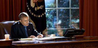 El presidente Obama sentado en un escritorio, escribiendo (La Casa Blanca/Pete Souza)