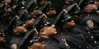 Rows of New York Police Department officers standing (© AP Images)