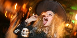 Woman dressed in witch costume sticking her tongue out (© AP Images)