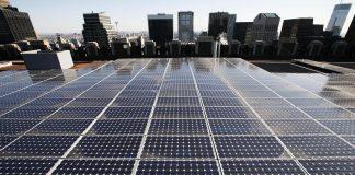 Painéis de energia solar instalados no telhado e arranha-céus ao fundo (© AP Images)