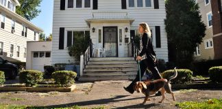 Woman walking with dog in front of house (© AP Images)