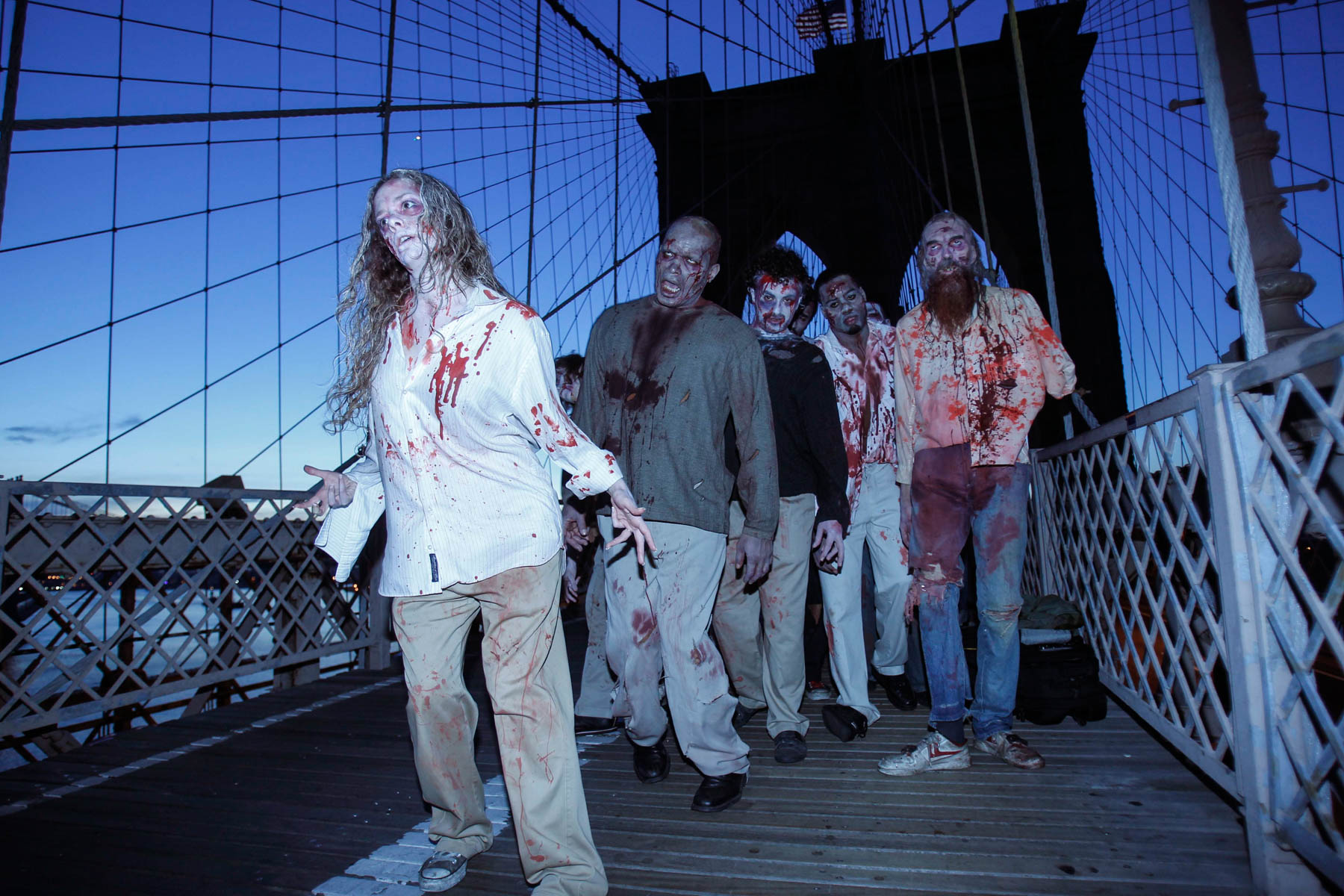 People dressed as zombies walking on bridge (© AP Images)