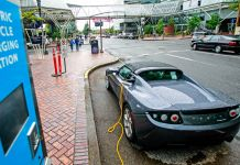 Electric car plugged into charging station (© AP Images)