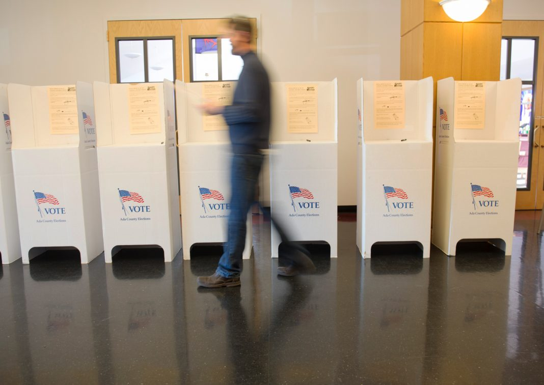 Blurred man walking past a row of voting booths (© AP Images)