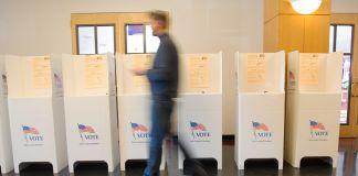 Silueta borrosa de un hombre que camina frente a una fila de cabinas para votar (© AP Images)