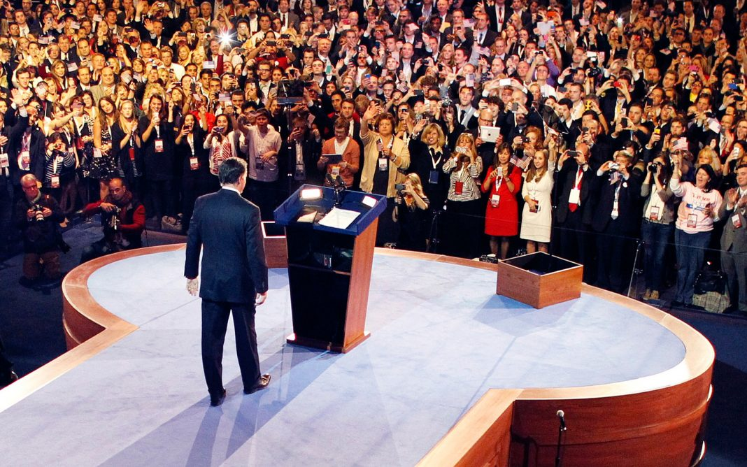 Man walking onstage toward podium before a standing audience (© AP Images)
