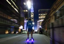 Person riding hoverboard at night (© AP Images)