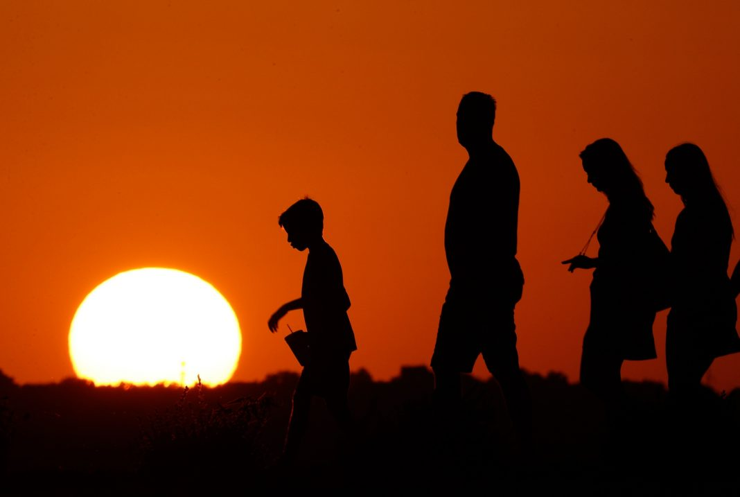 Sun setting showing shadows of four people walking (© AP Images)