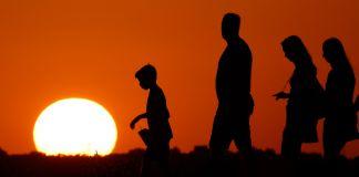 Silueta de cuatro personas caminando ante una puesta de sol (© AP Images)