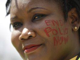 Woman with 'End Polio Now' written on her cheek (© AP Images)