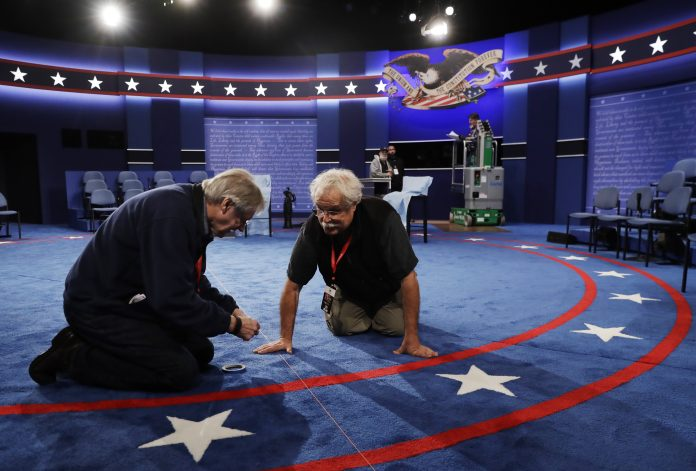Two people with roll of tape, kneeling in carpeted area (© AP Images)